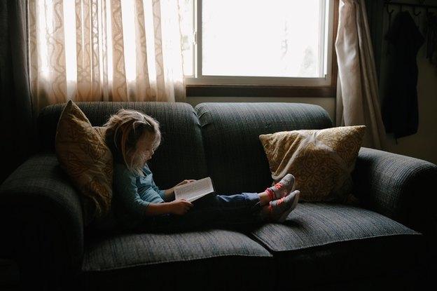 بچه روی کاناپه کتاب می خواند